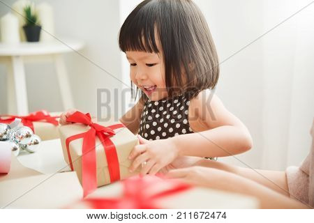 Cheerful Asian little kid celebrating with a brown gift box for Birthday Christmas and New year in a white room. Happy Asian family at the house. Copy space.