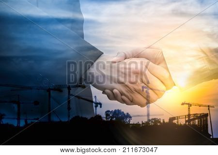 Double exposure. Businessman handshake on industrial background.