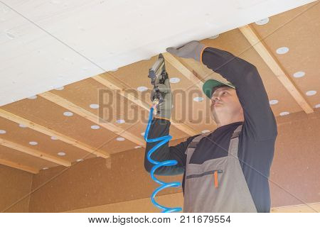 The worker produces finishing works of the ceiling with a white wooden board. Construction worker thermally insulating eco wooden frame house with wood fiber plates