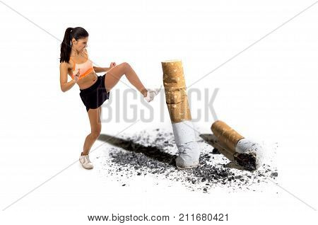 young attractive and furious latin sport woman in fight combat kick attacking angry against cigarette butt in stop and anti smoking advertising campaign concept and healthy lifestyle