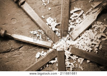 series of blade of sharp chisels with sawdust and sepia effect poster