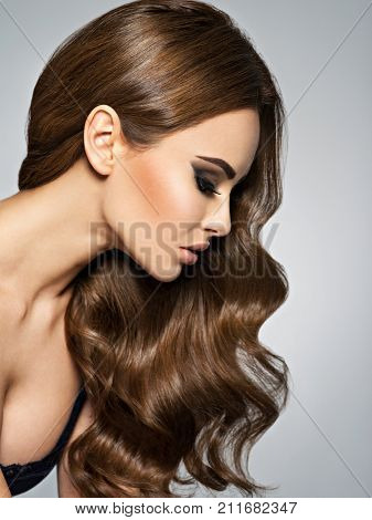 Beautiful caucasian woman with long brown curly hair. Profile Portrait of a pretty young adult girl.