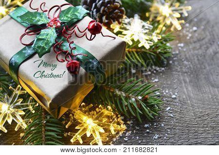 Merry Christmas.Christmas decoration with fir tree,gift box and garland lights on old wooden background.Winter holidays concept.Christmas background.Selective focus.