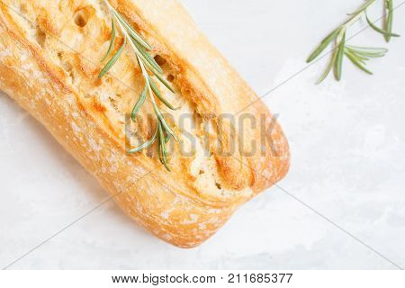 Fresh ciabatta with herbs on a light background top view.