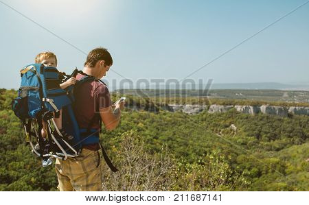 Young father with little son traveling in antic town in crimea. Baby sits in backpack on the shoulders of his dad. Man looking map in the phone.