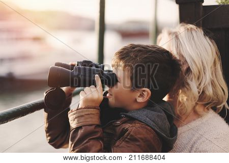 Happy little caucasian boy watching gazing searching for looking by binoculars with mother