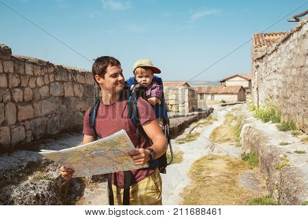 Young father with little son traveling in antic town in crimea. Baby sits in backpack on the shoulders of his dad. Man using paper map.