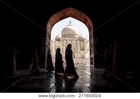 Argra Taj Mahal India - March 3 2012: Women in traditional saris passing arch in Taj Mahal in Agra Uttar Pradesh India