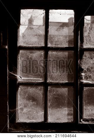 COBWEBS COVERING WINDOW IN DERELICT TEXTILE MILL YORKSHIRE ENGLAND