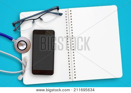 Flat lay of blue stethoscope glassesnotebok and mobile smart phone on navy blue background. Top view office desk with copy space for design and use. Business and healthcare medical concept.