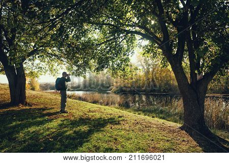 Man is watching birds with binoculars by the river in autumn. Intentionally toned.