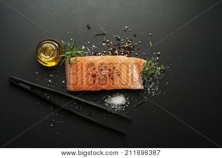 Raw steak of salmon fish with spices and herbs on black background