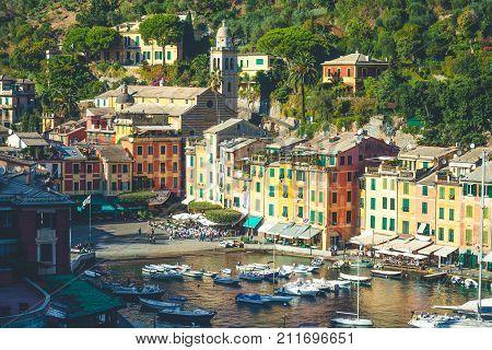 PORTOFINO, ITALY. October 20, 2017: Portofino in Italy, sea and coast. Piazza (Square) Martire dell'Olivetta, architecture with colorful buildings and tourists. Boats in the small marina port.
