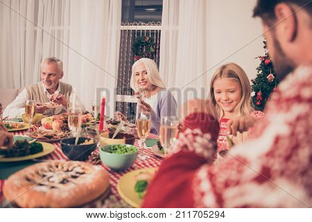 Cropped view of beautiful relatives married aged senior couple grandad granny cute small blond girl setted festive desktop full of yummy treats they wear knitted traditional x mas costumes enjoy