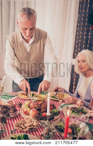 Bon appetite! Cheerful relatives setted festive desktop full of yummy treats grandad and granny in knitted casual wear enjoying food and company lights and curtains on background