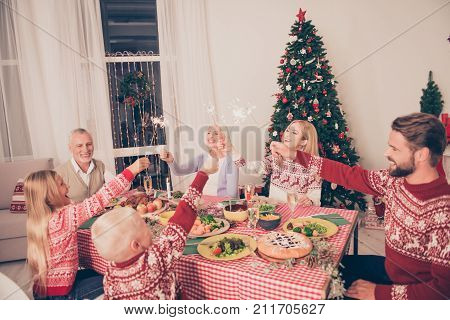 Six Gathered Cheerful Relatives Sit And Celebrate With Sparkles Up, Setted Festive Desktop With Tast