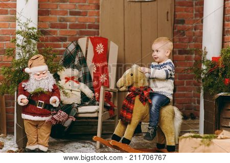 Playful Happy Cute Little Baby Boy On Rocking Horse, Dressed In Sweaters, Jeans And Boots In Decorat