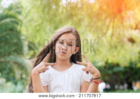 Conception of self-confidence. Flirting little girl making a V sign hand. Girl in the park.