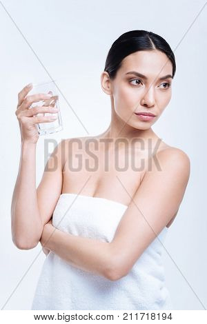 Low hydration level. Pleasant dark-haired young woman holding a glass of water, being about to drink it, while being wrapped into a towel