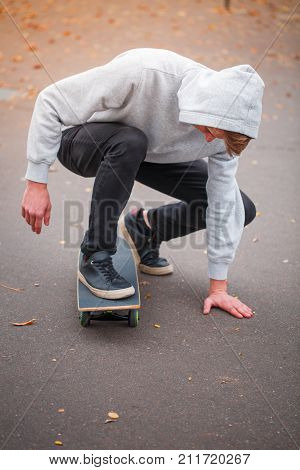 A young skateboarder practicing in a skate park. City concept about sport and skateboarding. A guy sitting on a skateboard.