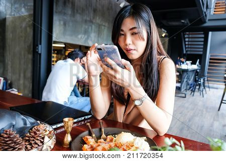 Women Texting On Moblie Phone While Sitting In Modern Cafe
