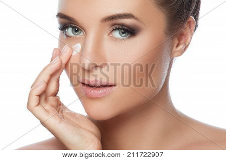 Young And Beautiful Woman Applying Moisturizing Cream On Her Face