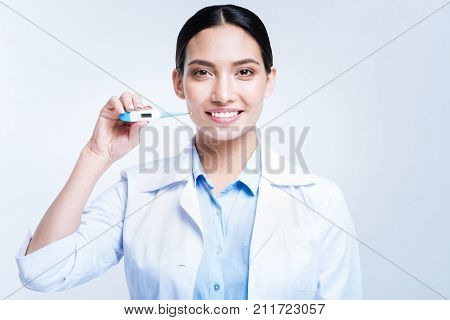 Thorough medical checkup. Pleasant cheerful woman in a medical uniform holding a thermometer and smiling at the camera while standing isolated on a white background