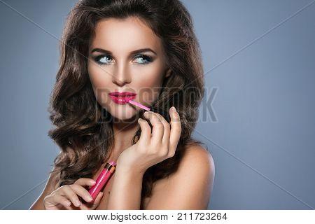 Beautiful young woman is applying pink lip-gloss