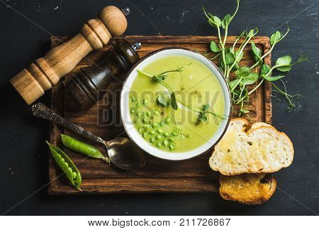 Fresh homemade pea cream soup in white bowl with grilled bread on wooden board over black slate stone backdrop, top view