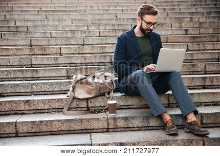 Portrait of young attractive man using laptop computer while sitting on stairs outdoors