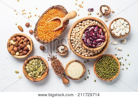 Vegan protein source. Legumes - lentils chickpeas beans green mung bean seeds and nuts on white background. Top view.