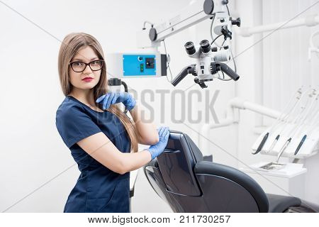 Portrait Of Young Female Dentist At The Morden Dental Clinic. Doctor Wearing Glasses, Blue Uniform,