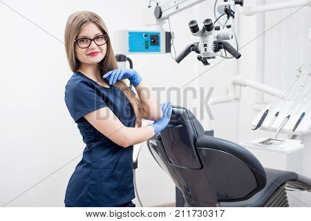 Portrait Of Smiling Female Dentist At The Morden Dental Office. Doctor Wearing Glasses, Blue Uniform