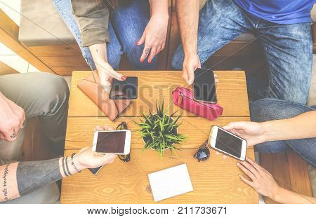 Top view of a group of hipster friends sitting in a bar cafe using mobile smart phone - New young generation trend - concept of people merged with phone technology - Focus on male hand on left