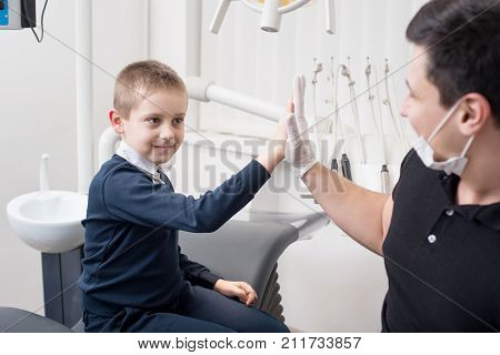 Pediatric Dentist Gives Five Young Boy, Congratulate Patient For A Successful Treatment In Dental Of
