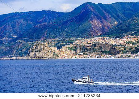 A Pilot Boat Along Mountainous Italian Coast in Strait of Messina