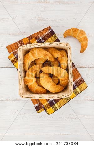 Basket of freshly baked homemade croissants on wooden background top view