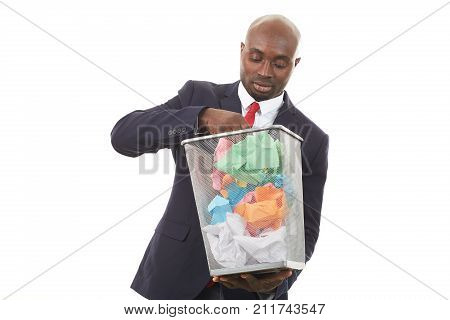 Portrait of African businessman searching document among crumpled papers in paper basket