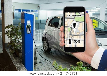 Hands with phone on a background of electric cars charging point. E-car sharing concept