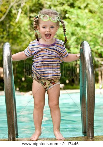 Baby in protective goggles leaves pool.Outdoor.