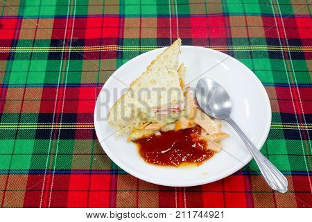 vegetables sandwiches serve with fried potato good food and healthy for diet and control weight with the tomatoes sauce on the white disc and the Stainless spoon on the Scottish chintz