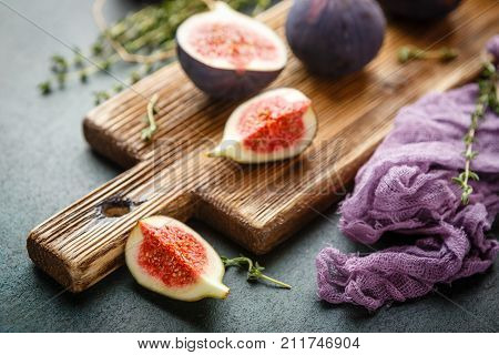 Juicy fresh whole fig fruits and one cut figs on wooden cutting board on dark green background
