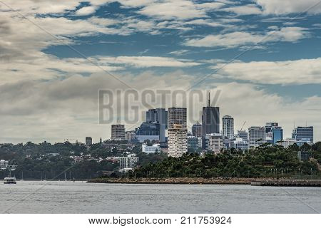 Sydney Australia - March 21 2017: Skyline of Kirribilli northern Sydney business district under blue sky with white clouds shows highrise office towers with harbor scenery and Millers Point park in front.