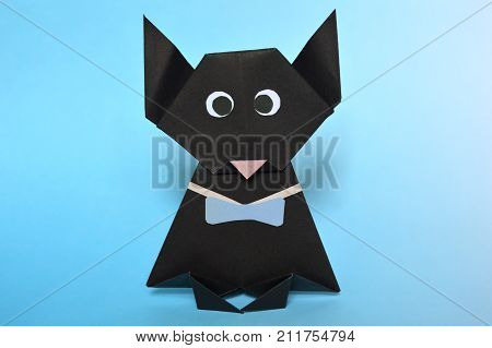 Origami black cat, paper folding, on blue background