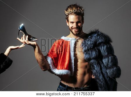 Freak gay and transvestite. Christmas guy in santa fur coat in crown. Cinderella prince with shoe on grey background. Drag queen homosexual and trans.