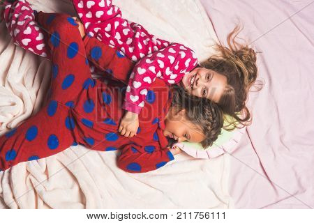 Children in pajamas happy smile in bed top view. Girl nightwear fashion. Bedtime slumber dream sleepover. Comfort home concept. Childhood family love friendship.