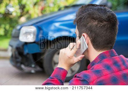 Man Reporting Car Crash On Mobile Phone