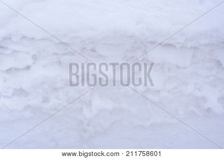 Natural background. Close-up fragment of white snowdrift with beautiful undulating structure.