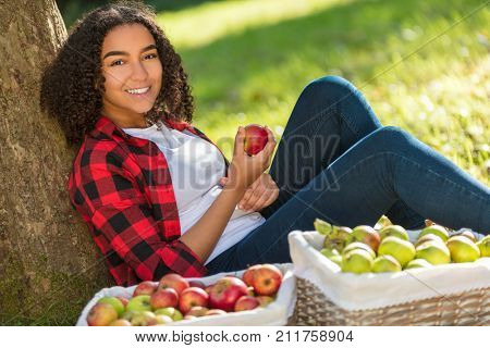 Beautiful happy mixed race African American girl teenager female young woman in an orchard eating an organic red apple, smiling with perfect teeth leaning against a tree with baskets of apples