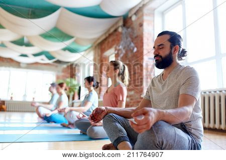 fitness, yoga and healthy lifestyle concept - man with group of people meditating in lotus pose at studio